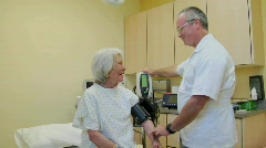 A medical professional takes the blood pressure of an elderly patient. Stock Footage