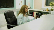 Stock Video Footage of A woman answers a phone behind the information desk of a hospital.
