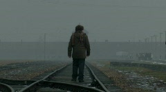 Auschwitz Birkenau main gate visitor walks on train line Stock Footage