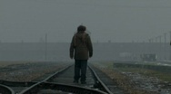 Stock Video Footage of Auschwitz Birkenau main gate visitor walks on train line