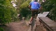 Mountain Bikers Jumping in Boardwalk Park Stock Footage