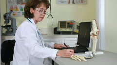 Woman doctor going over notes Stock Footage