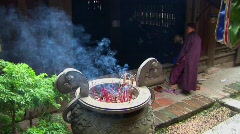 Monks gather as incense scents the air at a Vietnamese temple. Stock Footage