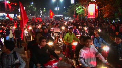 Motorcycles flying the Vietnamese flag crowd a boulevard Stock Footage