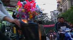 A woman walks with balloons through a busy street in Hanoi, Vietnam. - stock footage