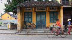 People and vehicles move by a small building in rural Vietnam. Stock Footage