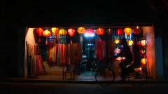 Bicycles and rickshaws pass a colorful lantern store at Stock Footage