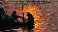 Vietnamese fishermen head out in their canoe at dusk. Stock Footage