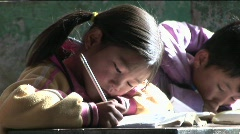 Children practice writing in a rural classroom in China. - stock footage