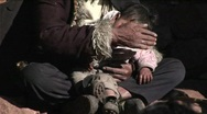Stock Video Footage of A small child sits in a poor beggars arms.