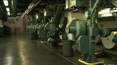 Workers watch paper rollers in newspaper factory. - stock footage