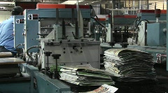 Workers man the printing presses in a newspaper factory. - stock footage