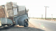 Stock Video Footage of An abandoned trailer sits along an empty highway.