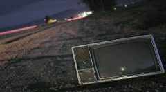 An abandoned TV set sits along a highway while traffic Stock Footage