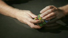 A time lapse shot of hands solving a Rubik's Cube puzzle. Stock Footage