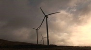 Backlit windmill generates electrical power on a hillside Stock Footage