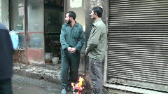 Two men warm their hands over a small fire on a street in Iran. Stock Footage