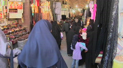 Women wearing headscarfs and chadors pass through a bazaar in Iran. Stock Footage