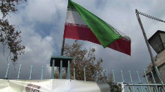 The Iranian flag flies atop a gate. - stock footage