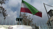 Stock Video Footage of The Iranian flag flies atop a gate.
