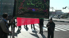 Protesters hold a sign at a busy intersection in Iran. Stock Footage