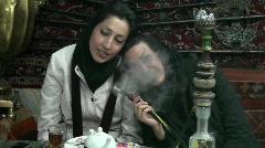 Women in headscarfs smoke a hookah pipe in a cafe in Iran. Stock Footage