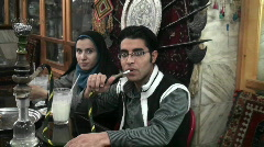 A woman wearing a headscarf and a man smoke a hookah pipe Stock Footage