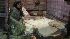 A woman wearing a headscarf bakes lavash bread on a tandori Stock Footage