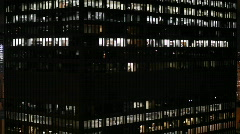 A large building has many lighted windows at night. Stock Footage