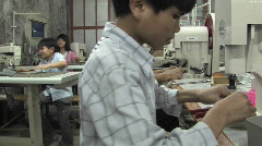 Asian youths sew in a factory. Stock Footage