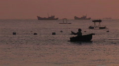 A man in a boat with ships in the background. Stock Footage
