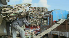 Man carrying heavy materials onto a truck. Stock Footage