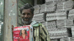 "An Indian newspaper and magazine salesman presents an issue of ""Good Stock Footage"