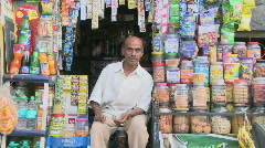 Asian shopkeeper sitting in his provision shop Stock Footage