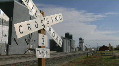 A railroad crossing sign stands near multiple grain silos. Stock Footage