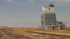 An abandoned grain elevator stands along a stretch of railway track. Stock Footage