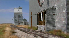 Abandoned grain elevators stand along a rusty stretch of Stock Footage
