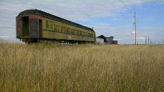 An old abandoned Pullman railway car sits in a field on a Stock Footage