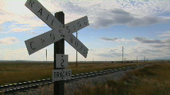 A railroad crossing sign rests stand next to old train tracks. Stock Footage