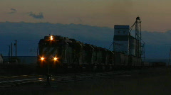 A freight train passes a grain silo at dusk. Stock Footage