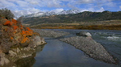 A small stream runs beneath snow covered mountains in Stock Footage