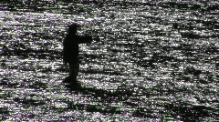 A man fly fishes in a broad shallow river. Stock Footage