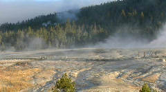 Tourists walk through a geothermal area at Yellowstone Stock Footage