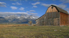 An old barn rises out of a prairie with the Grand Tetons in Stock Footage
