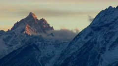 Sunlight shines on the peaks of a mountain pass in the Grand Tetons. Stock Footage