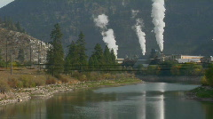 Smoke comes billowing out of a factory along a waterway. Stock Footage