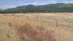 A wood and wire fence cuts through a dry grassland. - stock footage