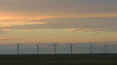 A line of windmills are silhouetted against a golden sky. Stock Footage