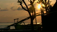 The sun sits low on the horizon behind a small fishing village. Stock Footage