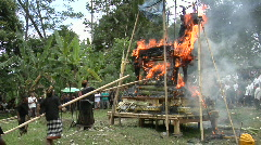 Men use long poles to poke at a funeral pyre during a Stock Footage